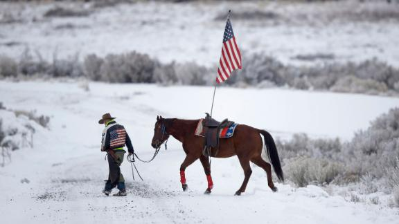 FILE - In this Jan. 7, 2016, file photo, cowboy Dwane Ehmer, of Irrigon, Ore., a supporter of the group occupying the Malheur National Wildlife Refuge, walks his horse near Burns, Ore. The last named defendant in the armed occupation of an Oregon wildlife refuge, not seen, was still at large Tuesday, March 22, 2016, drawing calls for supporters to flock to his Montana hometown and a local sheriff to urge outsiders to stay of it. (AP Photo/Rick Bowmer, File)
