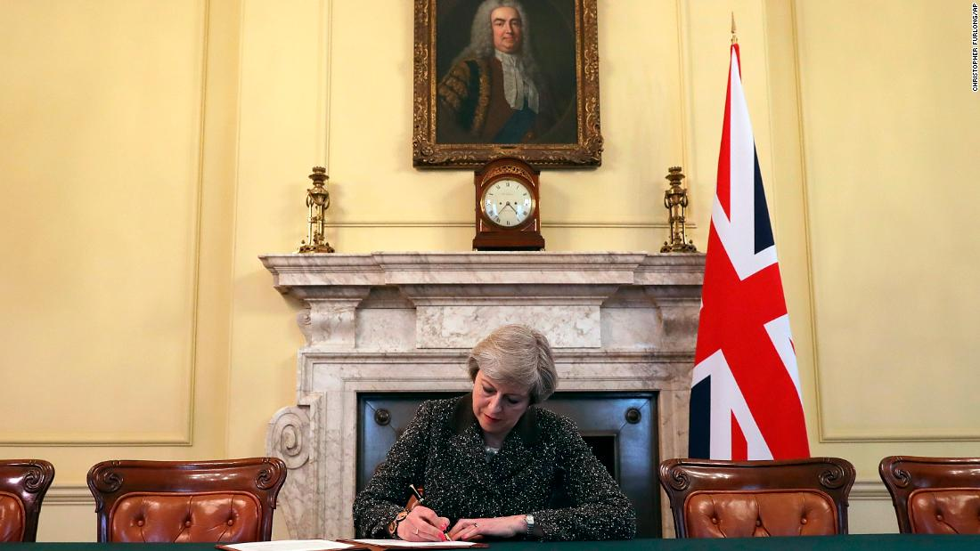 May signs a letter to European Council President Donald Tusk in March 2017 to start the formal process of Britain leaving the EU. She is sitting beneath a portrait of Robert Walpole, generally regarded as Britain's first Prime Minister.