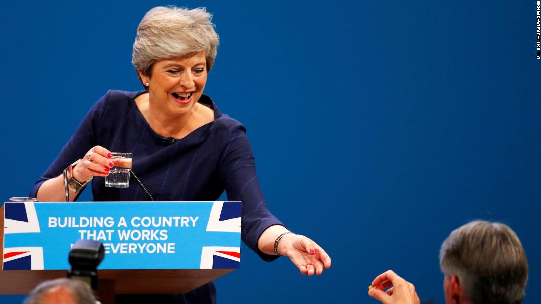 "May receives a cough drop from UK finance minister Philip Hammond while having a coughing fit in an address to a Conservative Party conference in Manchester in October 2017. Earlier in the speech, she was<a href=""https://www.cnn.com/2017/10/04/europe/theresa-may-speech-disaster-conservative-party-conference/index.html"" target=""_blank""> interrupted by a prankster,</a> who handed her a P45 form. A P45 is given to UK employees when they leave a company, similar to a pink slip in the United States."