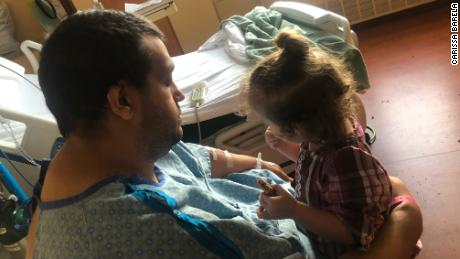 Barela, 30, holds his daughter Cataleya, now almost 2, during a hospitalization in January at Porter Adventist Hospital.