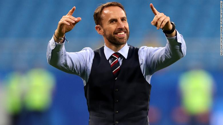 Gareth Southgate conducts the crowd as they sing a song to him.