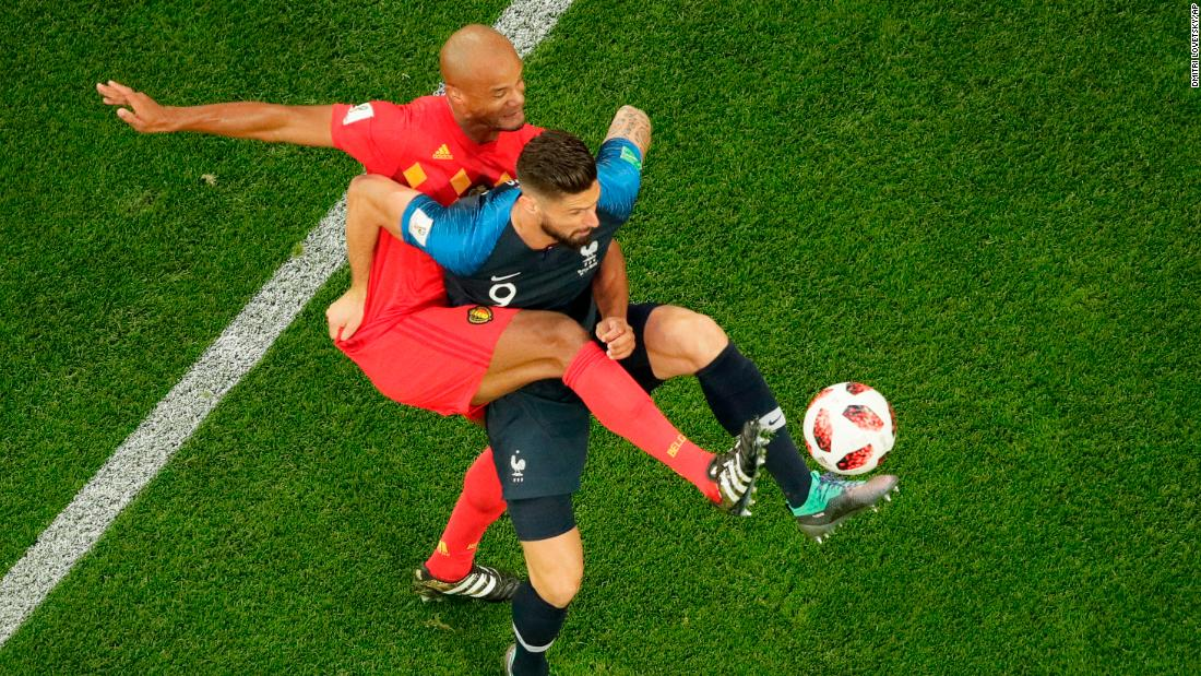 Giroud is challenged by Belgium defender Vincent Kompany.