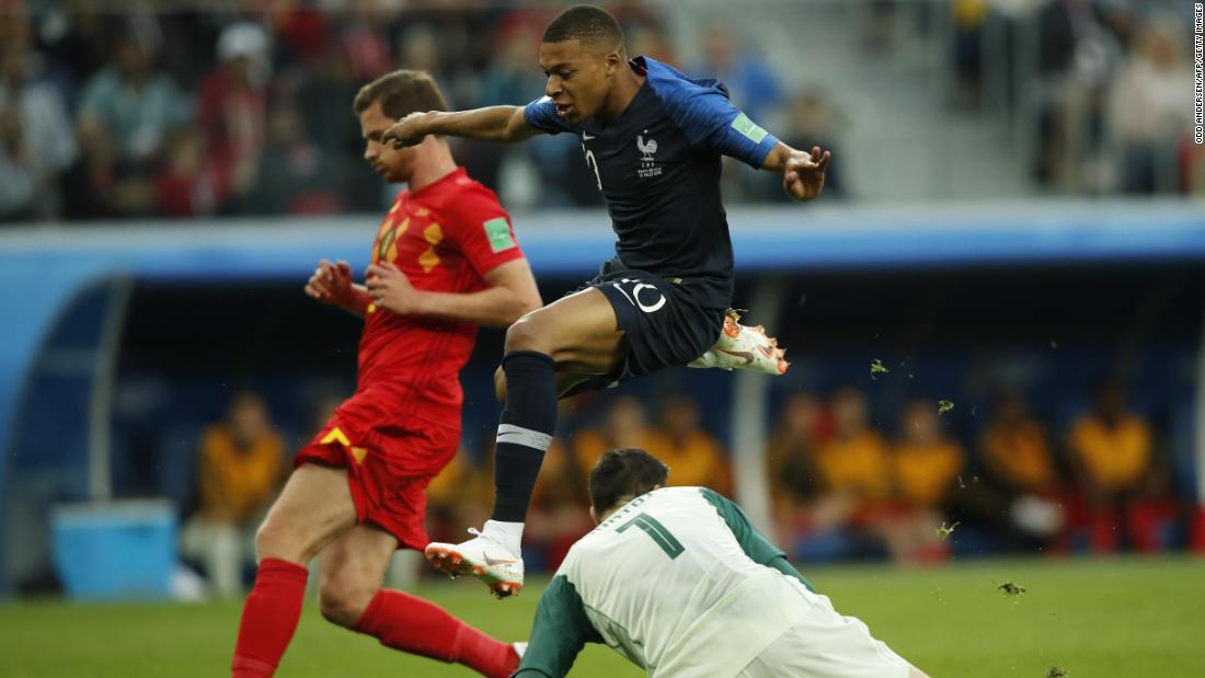 France's teenage sensation, Kylian Mbappe, jumps over Belgian goalkeeper Thibaut Courtois.