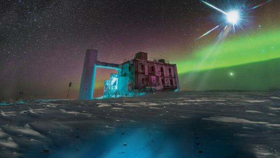 In this artistic rendering, based on a real image of the IceCube Lab at the South Pole, a distant source emits neutrinos that are detected below the ice by IceCube sensors.