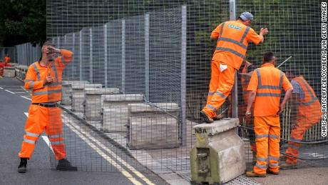 Workers install temporary security fencing outside Winfield House on Wednesday ahead of the visit of President Donald Trump.