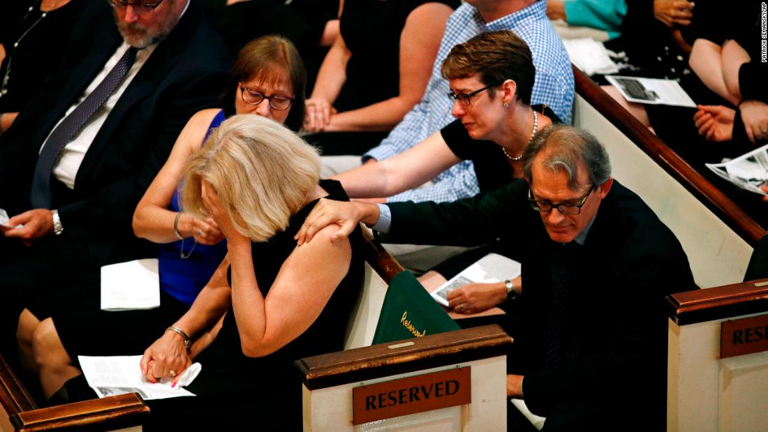 Andrea Chamblee is comforted during a memorial service for her husband, John McNamara, on Tuesday, July 10. McNamara was one of five people killed last month when a gunman opened fire in the newsroom of the Capital Gazette, a newspaper in Annapolis, Maryland.