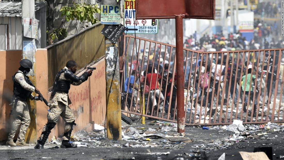 A police officer points his gun at people to avoid looting in shops in Delmas, Haiti, on Sunday, July 8. Protesters took to the streets after an increase in fuel prices ordered by the government.
