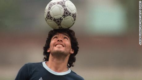 Argentine soccer star Diego Maradona, wearing a diamond earring, balances a soccer ball on his head as he walks off the practice field following the national selection's 22 May 1986 practice session in Mexico City. (Photo by JORGE DURAN / AFP)        (Photo credit should read JORGE DURAN/AFP/Getty Images)