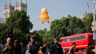The Trump 'blimp' floats next to the towers of Westminster Abbey.