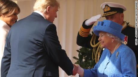 First Lady Melania Trump, left, stands by as US President Donald Trump shakes hands with Queen Elizabeth II as they arrive at Windsor Castle on Friday.