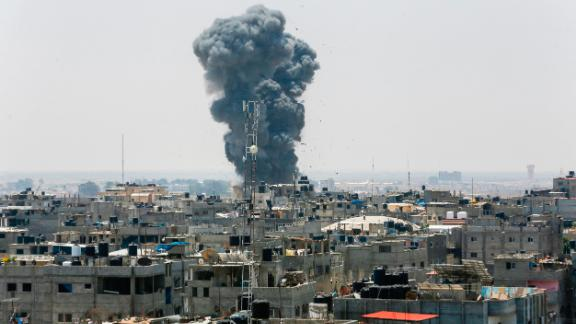 A picture taken on July 14, 2018 shows a smoke plume rising following an Israeli air strike in the southern Gaza Strip city of Rafah, near the border with Egypt. - Israel
