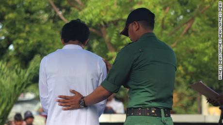 An official checks on a convicted offender during the public flogging.