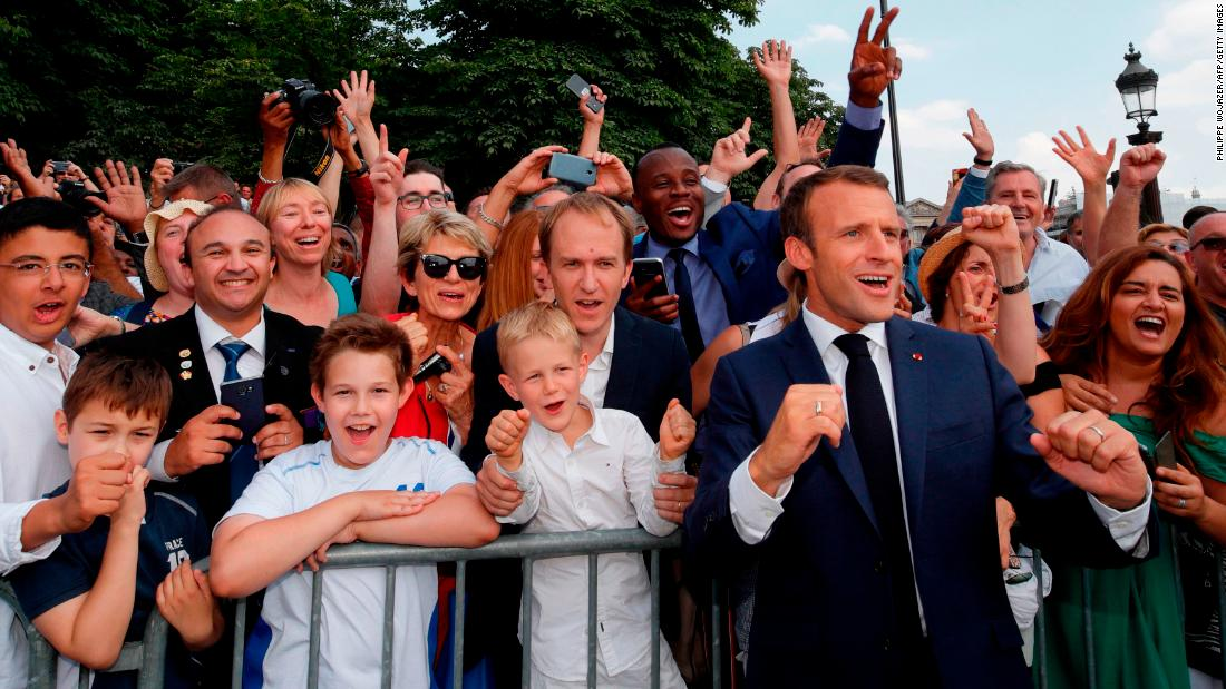 Macron joins a crowd of Bastille Day revelers as they cheer on the French national team on the eve of the World Cup final.