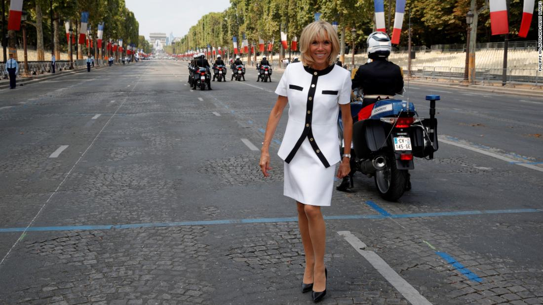 France's first lady, Brigitte Macron, poses on the Champs-Elysées Avenue after the Bastille Day military parade.