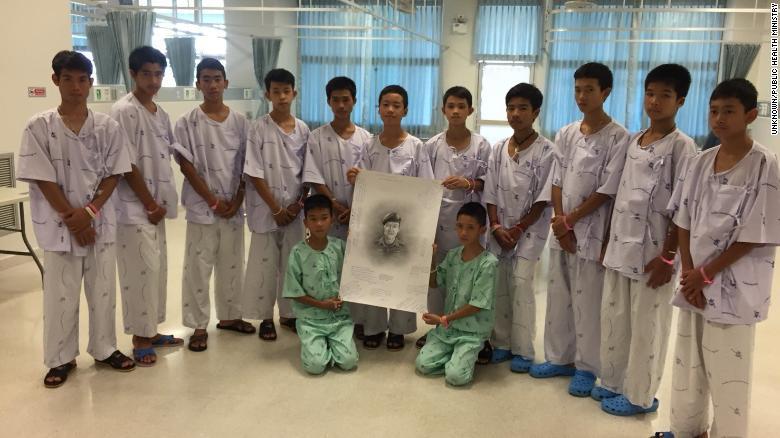 The Wild Boars soccer team hold a portrait of ex-Navy SEAL Saman Kunan.
