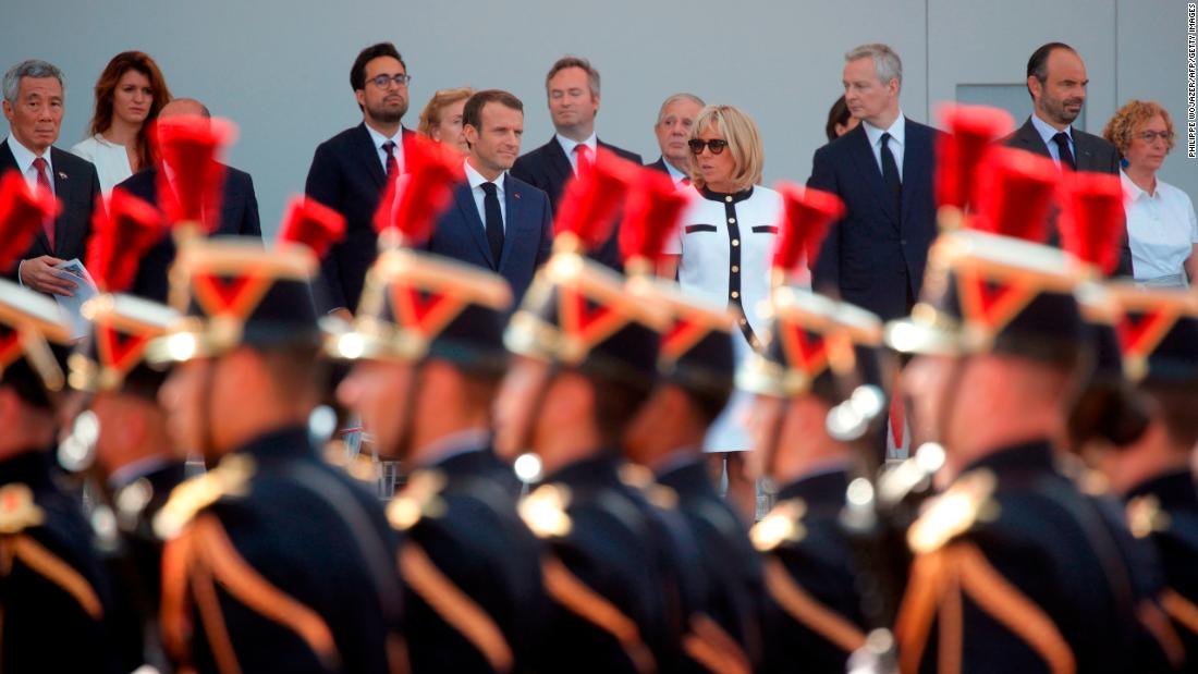 Singapore Prime Minister Lee Hsien Loong, far left, joins the Macrons and French officials for the military parade.