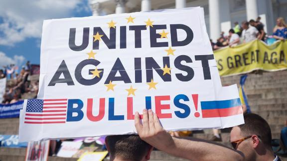 Protesters carried signs in Senate Square, protesting the policies of Donald Trump and Vladimir Putin.