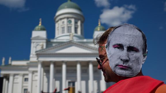 A protester wears a Vladimir Putin mask at the protest in Helsinki's Senate Square.