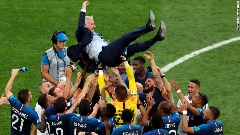 French players throw Deschamps into the air.