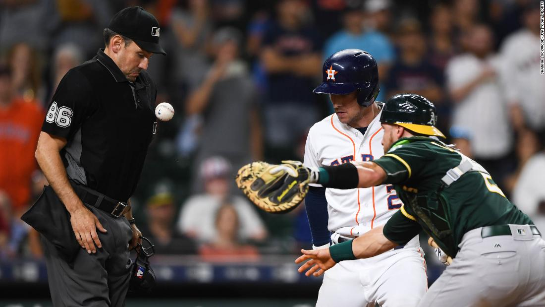 The baseball bounces off the chest of umpire David Rackley as Oakland Athletics catcher Jonathan Lucroy tries to tag out Houston Astros third baseman Alex Bregman at home plate during the eleventh inning in Houston on Tuesday, July 10.