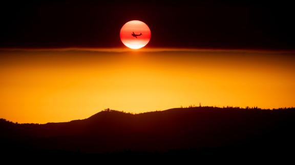 A plane battling the Ferguson Fire passes the setting sun near Yosemite National Park on Sunday.
