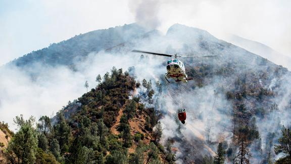 A helicopter flies over the growing Ferguson Fire on Saturday.