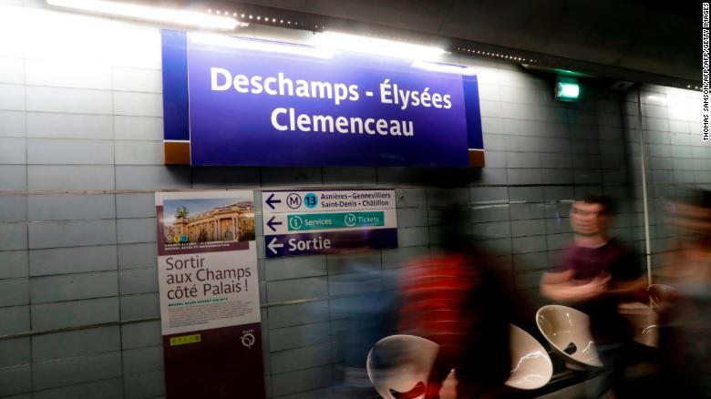 """Commuters walk past a sign reading """"Deschamps - Elysees Clemenceau."""""""