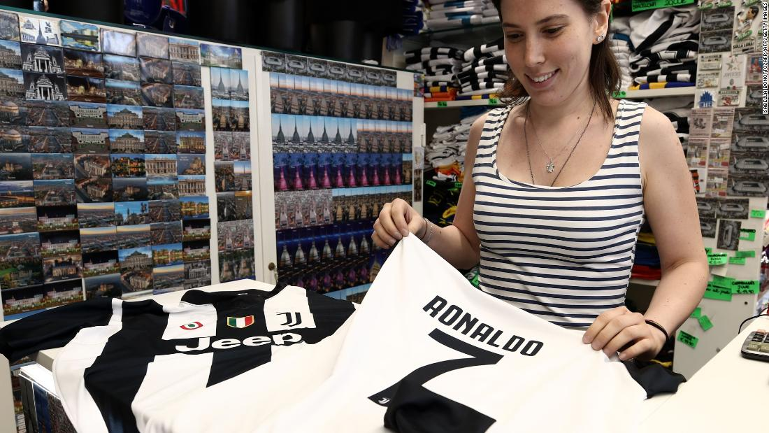 Juventus is already reaping commercial rewards from Ronaldo's signing, with a reported estimate of 520,000 replica jerseys flying off the shelves and online. This photo shows a saleswoman folding the famous No. 7 jersey at Juventus' flagship Turin store on July 11, the day after the deal was announced.