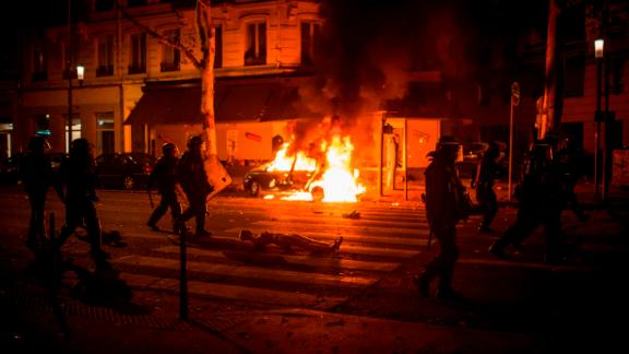 French anti-riot police officers walk by a burning car during clashes in Lyon on Sunday night.