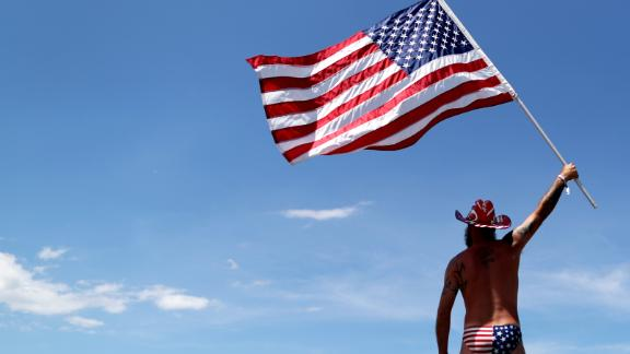 DAYTONA BEACH, FL - JULY 07:  A fan waves an American Flag in the infield prior to the Monster Energy NASCAR Cup Series Coke Zero Sugar 400 at Daytona International Speedway on July 7, 2018 in Daytona Beach, Florida.  (Photo by Sean Gardner/Getty Images)