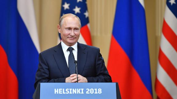 "Russia's President Vladimir Putin smiles during a joint press conference with US President after a meeting at the Presidential Palace in Helsinki, on July 16, 2018. - The US and Russian leaders opened an historic summit in Helsinki, with Donald Trump promising an ""extraordinary relationship"" and Vladimir Putin saying it was high time to thrash out disputes around the world. (Photo by Yuri KADOBNOV / AFP)"