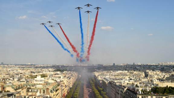The Patrouille de France jets trail smoke in the colours of the national flag while they fly over the Champs Elysee.