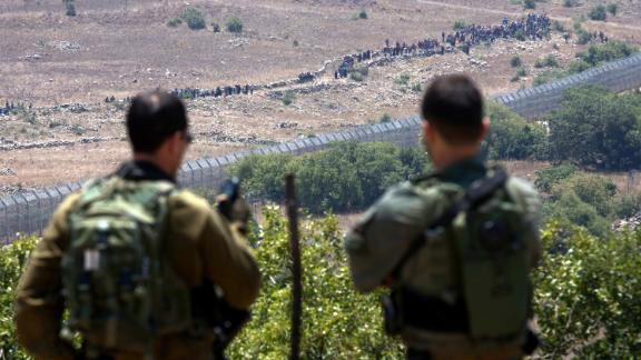 Israeli soldiers look on as Syrian refugees march towards the security fence in the Golan Heights on Tuesday.
