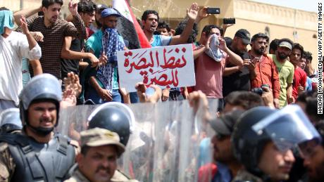 Iraqi security forces form a human barrier as protesters demonstrate against unemployment and a lack of basic services in the southern Iraqi city of Basra, on Sunday, July 15.