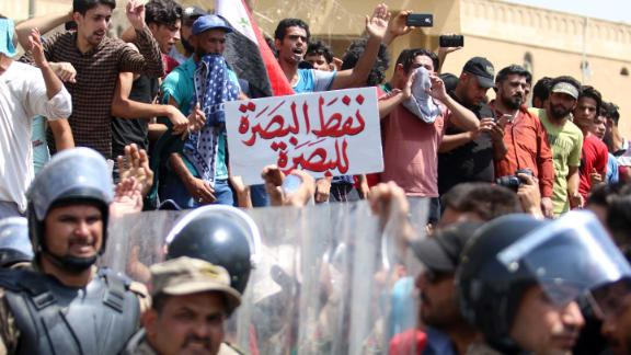 """Iraqi security forces form a human barrier as protesters demonstrate against unemployment and a lack of basic services in the southern Iraqi city of Basra on July 15, 2018. The banner reads in Arabic """"Basra's oil belongs to Basra"""". - Dozens of demonstrators were wounded today as the ongoing protests hit several Iraqi provinces including Basra, despite Prime Minister Haider al-Abadi announcing fresh funds and pledges of investment for the oil-rich but neglected region. (Photo by Haidar MOHAMMED ALI / AFP)        (Photo credit should read HAIDAR MOHAMMED ALI/AFP/Getty Images)"""