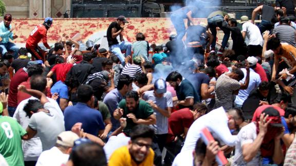 Protesters react as Iraqi security forces fire tear gas during a demonstration against unemployment and a lack of basic services in the southern Iraqi city of Basra, on Sunday, July 15.