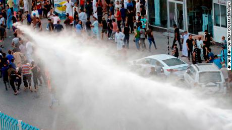 Iraqi security forces spray demonstrators with a water canon during protests in the city of Najaf, on Saturday, July 14.