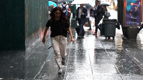 People take cover in Midtown New York on July 17, 2018 as a sudden storm hit the area with flash food warning in the tri-state area. Timothy A. Clary/AFP/Getty Images