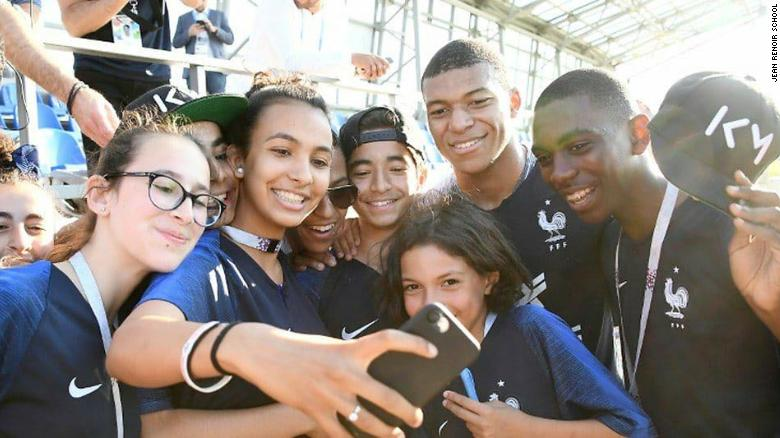 Kylian Mbappe poses for a photo with the pupils from school Jean Renoir.