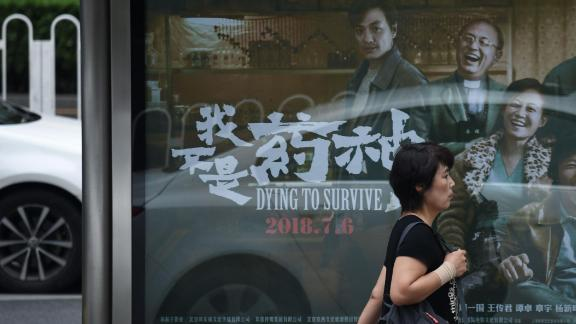 """A woman walks past a poster of the film """"Dying to Survive"""" at a bus stop in Beijing on July 12."""