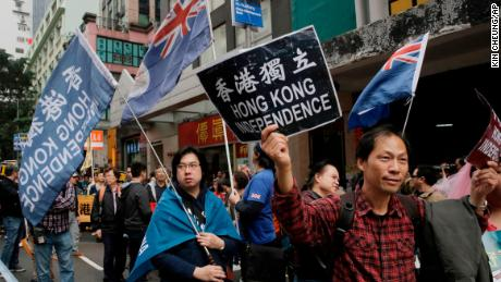 Pro-independence protesters hold placard and wave Hong Kong colonial flags during a rally in Hong Kong on January 1, 2018.