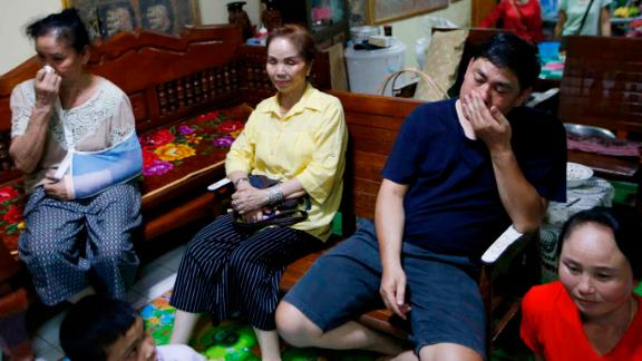 Relatives of Duangpetch Promthep, one of the rescued boys, watch the press conference live on television.
