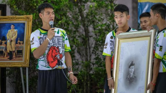 Coach Ekkapol Chantawong, left, pays tribute to Saman Kunan, the Thai Navy SEAL who died during the resuce attempt.