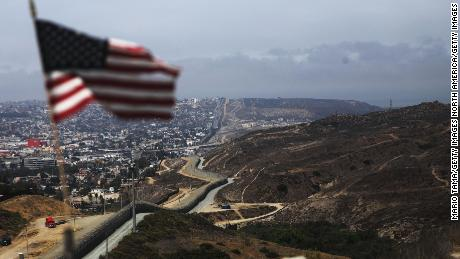 An American flag flies along a section of the Mexico border fence in San Diego.