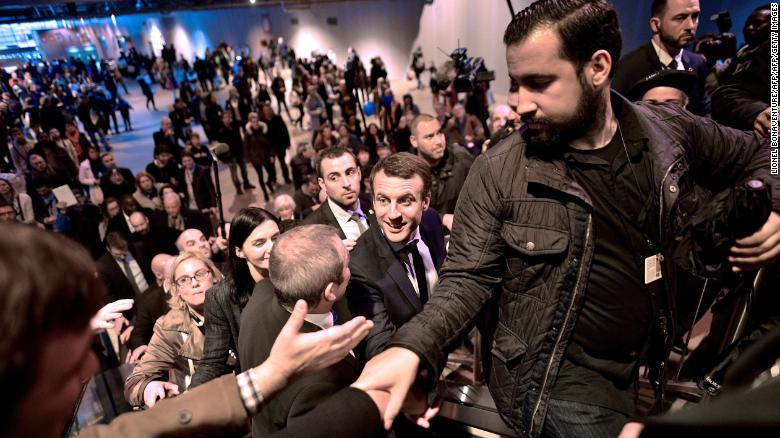 Emmanuel Macron, centre, shakes hands as he visits Paris' international agriculture fair in March 2017 as his head of security Alexandre Benalla, right, clears the way.