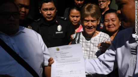 Australian nun Patricia Fox is escorted by immigration officers in Manila in April, a day after she was arrested.