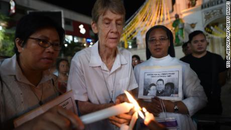Australian nun Patricia Fox lights a candle as she attends a prayer vigil in Manila in June.
