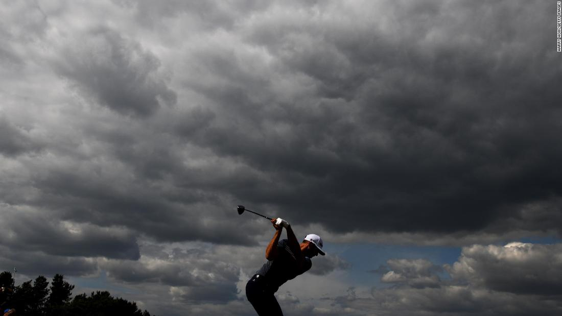 Dustin Johnson plays his tee shot on the ninth hole Thursday. The dark clouds symbolized his tough first round (5-over). He ended up missing the cut.