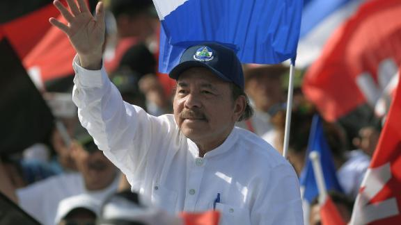 """Nicaraguan President Daniel Ortega waves to supporters, as he arrives to take part in the commemoration of the 39th Anniversary of the Sandinista Revolution at """"La Fe"""" square in Managua on July 19, 2018. - Nicaragua on Thursday marked the anniversary of its leftwing Sandinista revolution victory 39 years ago -- but the commemorations were overshadowed by President Daniel Ortega's deadly crackdown on opponents calling for his ouster. (Photo by MARVIN RECINOS / AFP)        (Photo credit should read MARVIN RECINOS/AFP/Getty Images)"""