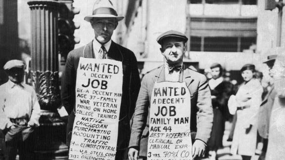 Two men wearing sandwich boards advertising their willingness to find employment -